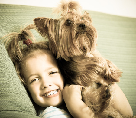 Female child playing with charming Yorkie at home Imagens