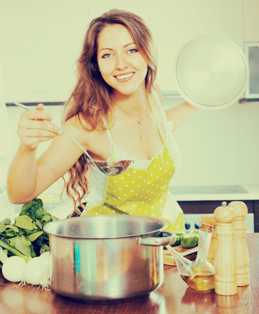 Smiling young housewife in apron cooking vegetable soup in home kitchen