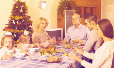 Big united family at festive table near Christmas tree