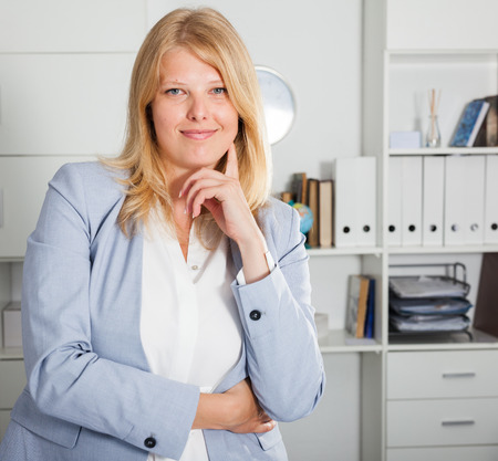Business lady with positive look and cheerful smile on modern office background Stock Photo