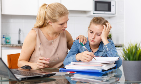Mother calming her daughter who upset by her studies at kitchen table