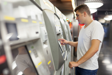 Portrait of young confident man in white shirt purchasing ticket at terminal in metro station Standard-Bild