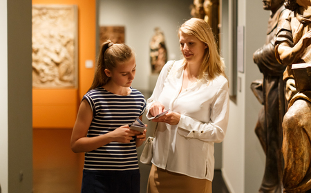 Young woman visitor with daughter with guide book looking at exhibition in museum of ancient sculpture
