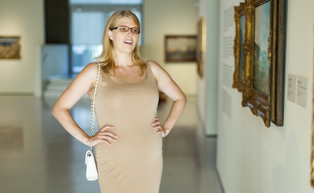 Positive woman wearing glasses standing at hall of museum and looking at painting