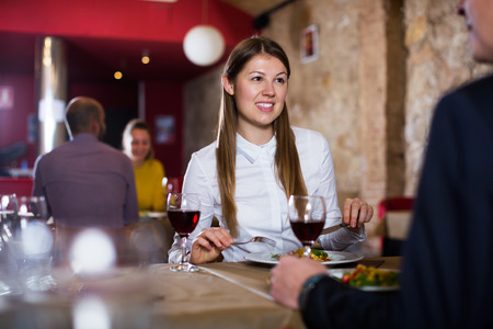 happy woman with male colleague on friendly meeting over dinner with wine in restaurant