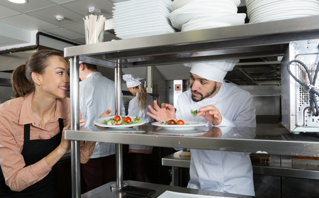 Head chef checking dishes in kitchen of restaurant before serving guests