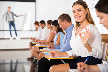 Cheerful girl student gesturing ok sign while listening to lecture in auditorium with groupmates, side view