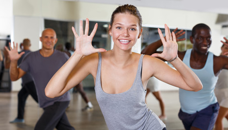 Group of active young woman and men practicing modern dance together in studio