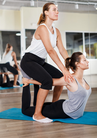 Group of sporty people doing a stretching exercises in pairs before dance training in a modern studio Stock Photo