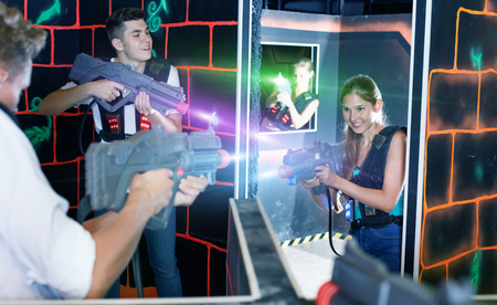 Laser tag players  cheerful  guys and girls playing in teams in dark laser tag room