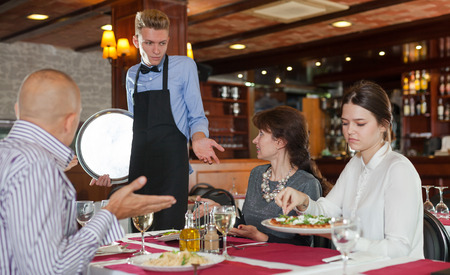 Dissatisfied guests complaining to young waiter about food and service in restaurant