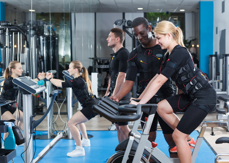 Smiling female and male athletes in EMS suit exercising in modern gym