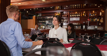 Smiling young woman visiting restaurant with her husband, discussing menu at table