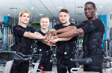Team of confident sporty young l positive people dressed EMS vests in modern fitness gym Stock Photo