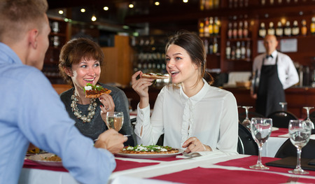 Successful business women with man partner having dinner and drinking wine in restaurant