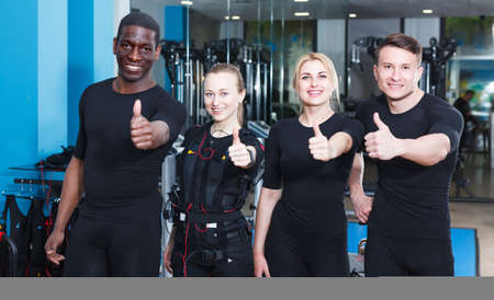 Active people in top shape taking break during EMS workout at gym, posing together Stock Photo