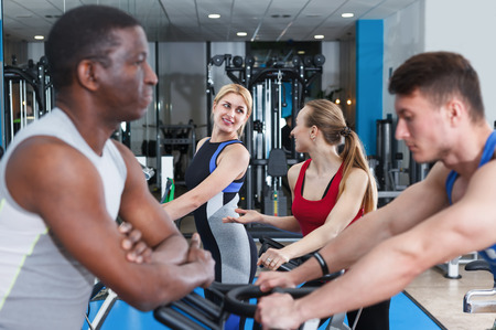 Positive men and girls talking while training in fitness gym Stock Photo