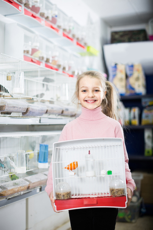 Smiling spanish  girl customer happy about buying cage with canary bird in pet shop Banque d'images