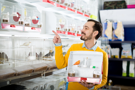 Young smiling man choosing pretty bird for keeping in pet shop Stock Photo