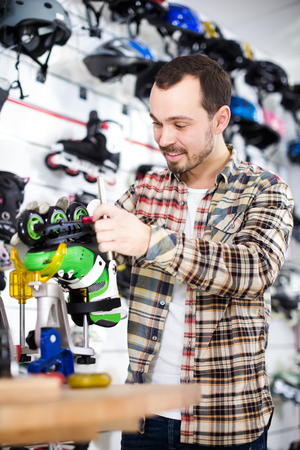 Smiling young guy master fixing roller-skates in sports store