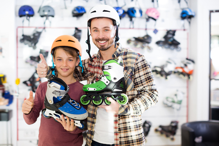 Adult father and son boasting purchased roller-skates in sports store