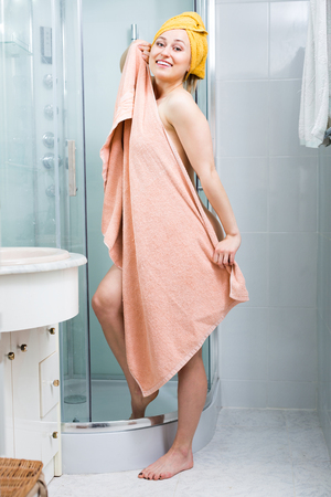 Sexy smiling young woman wrapped in towel after shower posing in bathroom