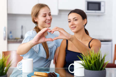 Young smiling emotional girlfriends showing the heart with hands and drinking tea at table Reklamní fotografie