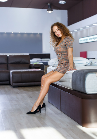 Young smiling woman testing new mattress in modern furniture store