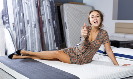 Portrait of young female customer with thumbs up satisfied with quality of mattresses in furniture salon Stockfoto