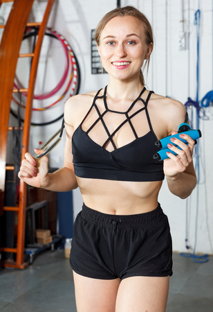 Cheerful attractive girl taking break during workout at gym, posing with skipping rope