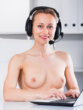 Young smiling naked girl talking on the headset in the office