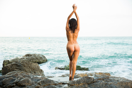 Portrait of absolutely naked girl standing in sensual pose on rock near sea Stock fotó