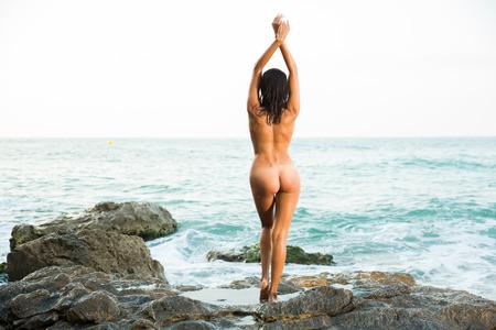Retrato de absolutamente niña de pie en pose sensual sobre roca cerca del mar