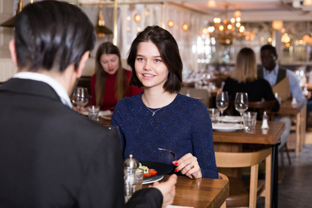 Portrait of couple who is dining and drinking wine in luxurious restaurant.