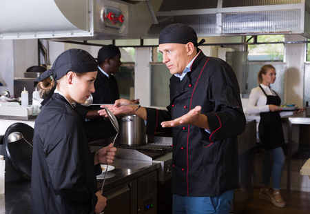 Angry male chef talking to his female assistant in commercial kitchen Stock fotó