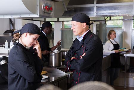 Exasperated head chef scolding upset female employee in kitchen of restaurant Stock fotó