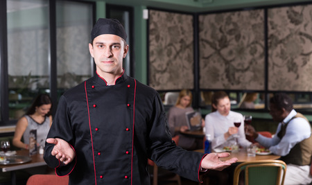 Portrait of professional chef meeting restaurant guests