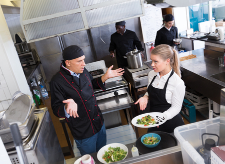 Young waitress standing with cooked dish in restaurant kitchen talking with puzzled male chef