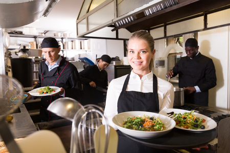 Smiling young waitress holding delicious cooked meals in restaurant kitchen Фото со стока