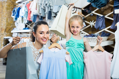 charming mother with daughter buying kids clothes in shop Imagens