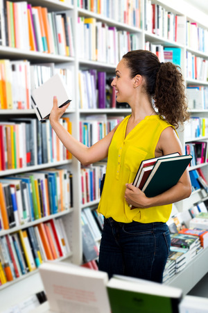 Smiling woman taking literature books in store with prints