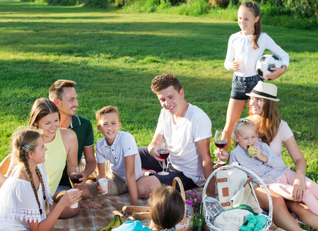 Two cheerful families with kids gaily spending time together at picnic in nature