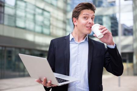 Cheerful  businessman with laptop and coffee standing in the street Stock Photo