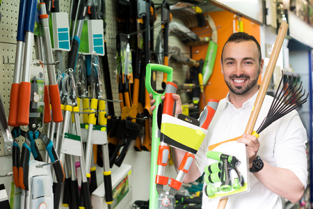 Young smiling man standing next to shop stall with gardening tools in  household store