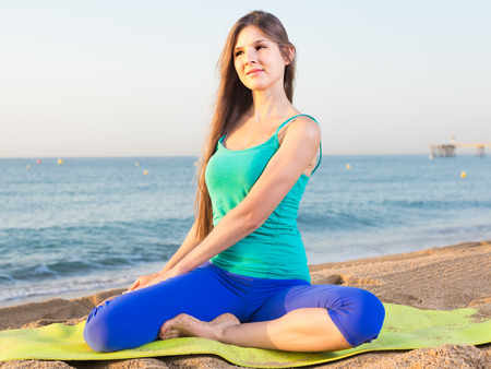 Young woman in blue T-shirt is sitting and practicing asana on nature.