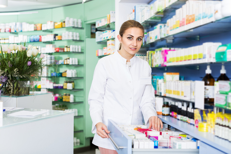 Female specialist is attentively looking medicines in lockers in pharmacy 免版税图像