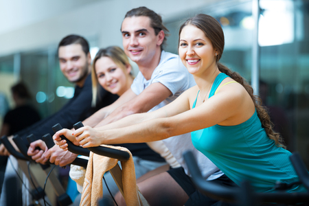 Group of people training on exercise bikes in gym Imagens