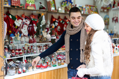 Young man and long-haired woman  at Christmas market.