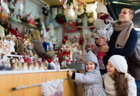 Happy family of four at Christmas market. Selective focus on woman Stock Photo