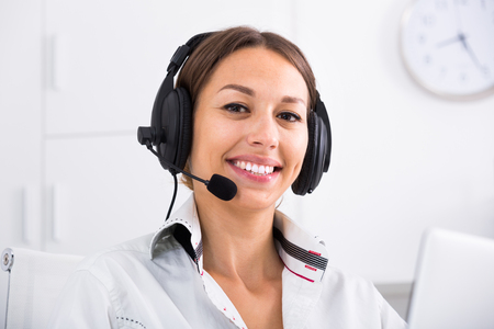 portrait of cheerful woman with headset on answering at company office